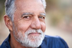 Outdoor Portrait Of Serious Hispanic Senior Man With Mental Health Concerns